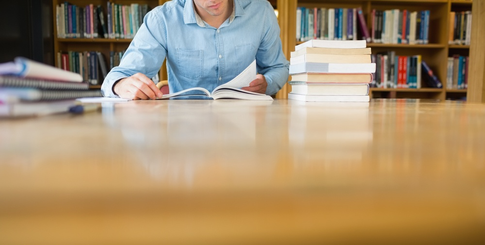 Mid section of a mature male student studying at desk in the library